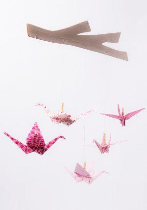 מובייל עגורים בגוונים ורודים ולבנים בהדפסים שונים עשויים בד כותנה ומחוברים למתלה עץ בלזה החתוך בצורת ענף - מובייל לעיצוב חדר הילדים, מתנת לידה, מובייל לשידת ההחתלה, מובייל התפתחותי, מובייל לתינוק, מובייל ורוד, מורן אלחלל אוריגמי בד