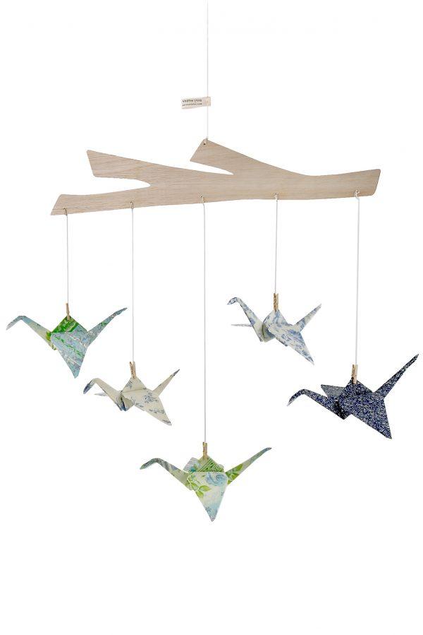 מובייל לתינוק ולחדר הילדים ובו 5 עגורי אוריגמי עשויים בדי כותנה ב5 גוונים שונים ממשפחת הירוקים והכחולים המחוברים למתלה עץ טבעי החתוך בצורת ענף, מובייל התפתחותי לתינוק, מורן אלחלל, אוריגמי בד
