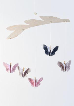 מובייל פרפרי אוריגמי בד משולב עם מתלה עץ בלזה בחיתוך בצורת ענף עם עלים. מתנת לידה מיוחדת בעבודת יד, מושלם לעיצוב חדר הילדים. מובייל אינטראקטיבי והתפתחותי. מורן אלחלל אוריגמי בד.
