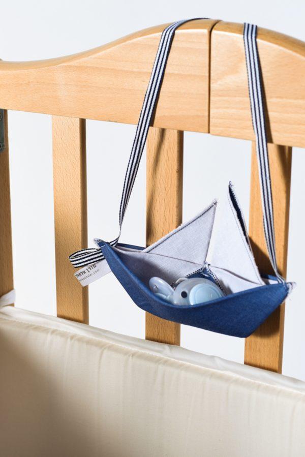תלה מוצצים למיטת תינוק, מתלה בצורת סירת מפרש בבד כחול ג'ינס, לתלייה ולשמירה על המוצצים בלילה, משמש גם כחפץ מעבר וצעצוע לתינוק. מורן אלחלל אוריגמי בד.