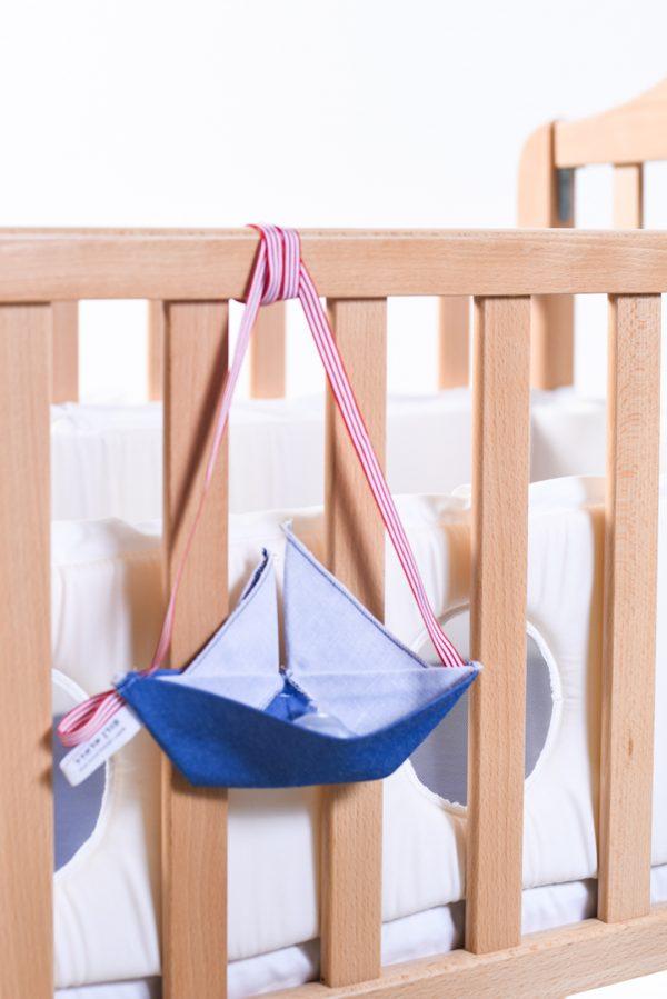 מתלה מוצצים למיטת תינוק, מתלה בצורת סירת מפרש בבד כחול גקינס, לתלייה ולשמירה על המוצצים בלילה, משמש גם כחפץ מעבר וצעצוע לתינוק, מתנת לידה, מתנה לתינוק, מתנה לגיל שנה. מורן אלחלל אוריגמי בד.