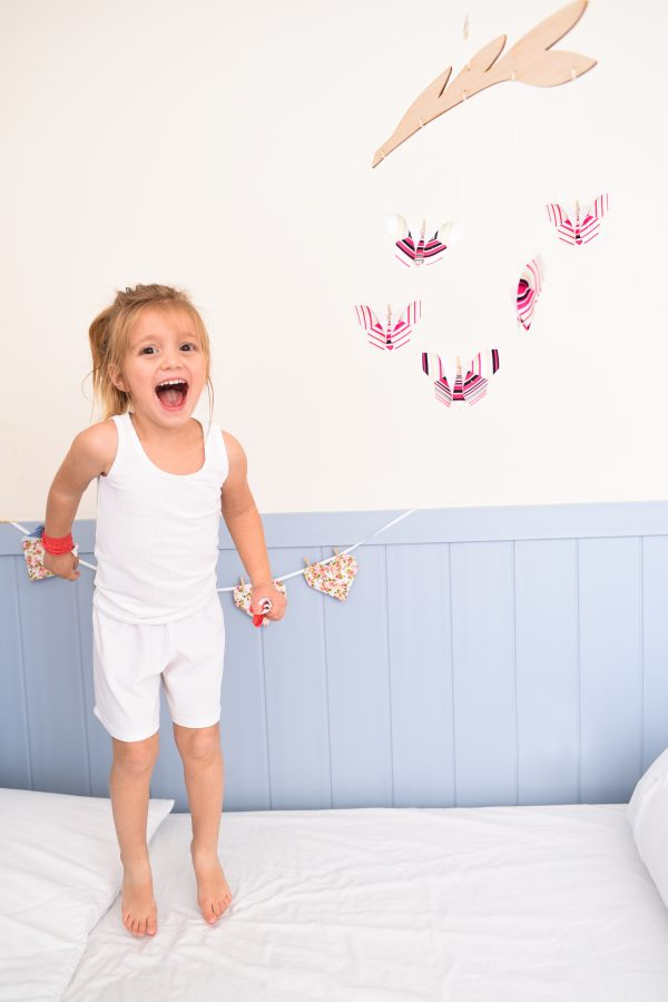 מובייל פרפרים לעיצוב חדר הילדים, תלוי מעל המיטה עם מתלה בצורת ענף ואליו מחוברים בעזרת אטבים פרפרי בד הצבעים שונים המקופלים ותפורים בשיטת האוריגמי. מתנה לעיצוב חדר הילדים, מתנת לידה או מובייל לתינוק. מורן אלחלל אוריגמי בד