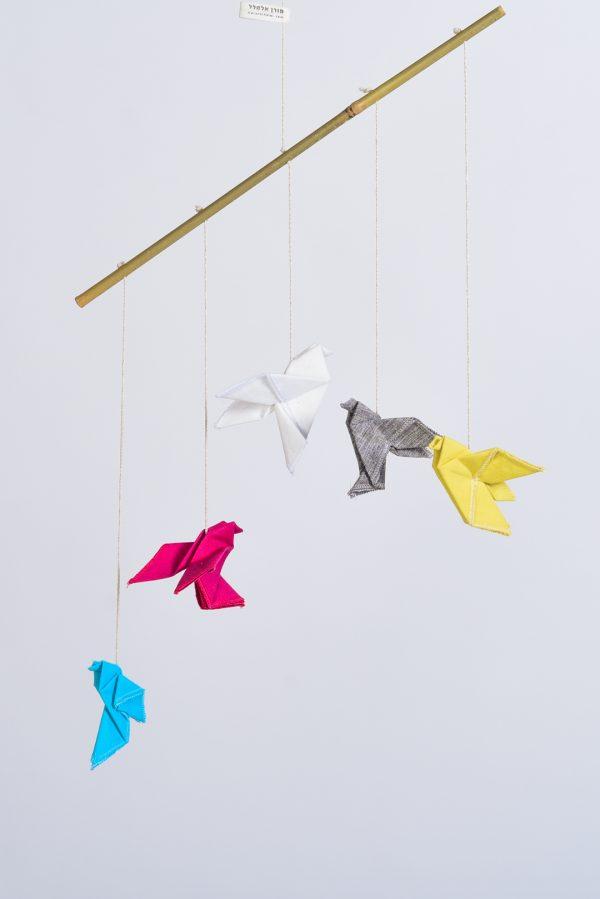 מובייל ובו חמישה ציפורי אוריגמי מקופלות ות]ורות מבדי פשתן בצבעים, ורוד , אפור, צהוב, לבן ותכלת ומחוברות למוט במבוק טבעי. מתנהת לידה מיוחדת לעיצוב חדר הילדים, מובייל לתינוק ולעיצוב הבית. מורן אלחלל אוריגמי בד