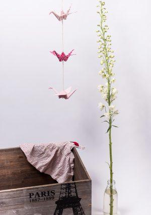 גרלנדה אנכית שלושה עגורי אוריגמי בשילובי בדים בגוונים ורודים ולבנים תלויים על חבל כותנה בגוון שמנת. מתנת לידה, לעיצוב חדר הילדים. מורן אלחלל אוריגמי בד.