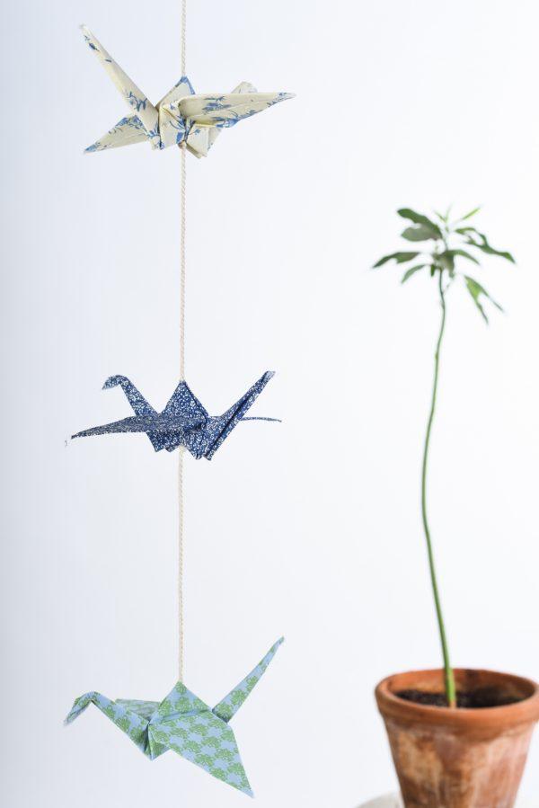 גרלנת עגורים לעיצוב חדר הילדים, מתנת לידה ומתנת יום הולדת. בגרלנדה 3 עגורים בגוונים של כחול שמנת וירוק טורקיז תלויים בצורה אנכית . מורן אלחלל אוריגמי בד.