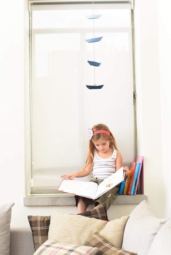 ילדה קוראת ספר עם סרט פרפר על הראש ומאחוריה גרלנדת סירות אוריגמי מבד ג'ינס כחול לעיצוב הבית.