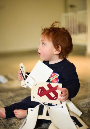 אותיות מעוצבות לתלייה עם סימנים נוספים מעוצבים. בדי כותנה מקולפי לאותיות בשפת האוריגמי על גבי דגלי קנווס מלבניים לתלייה ולעיצוב חדר הילדים. מורן אלחלל אוריגמי בד