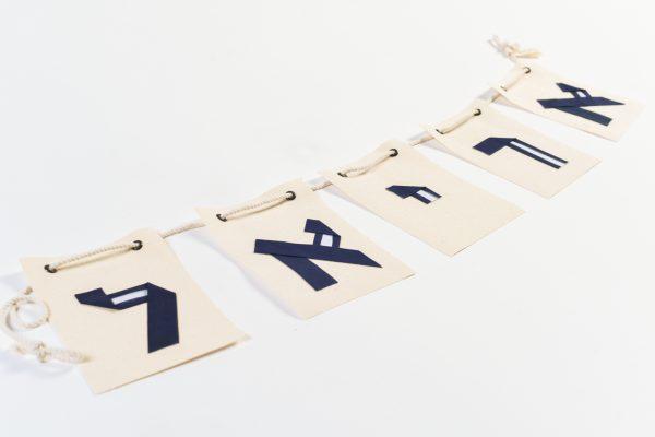 שרשרת שם הילד לתלייה על הקיר, אותיות אוריגמי מעוצבות מבדי כותנה על גבי דגלי קנבס מלבניים. מתנת לידה, מתנת יום הולדת, אותיות מעוצבות. מורן אלחלל אוריגמי בד.