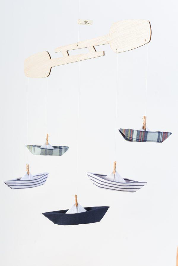 מובייל סירות לתינוק, לעיצוב חדר הילדים. מתלה חתוך מעץ בלזה בגוון טבעי בצורת זוג משוטים אליו מחוברות בעזרתאטבי עץ 5 סירות אוריגמי בד כותנה בגוונים של כחול בהספדים חלקים, פסים ומשובצים. מורן אלחלל אוריגמי בד .