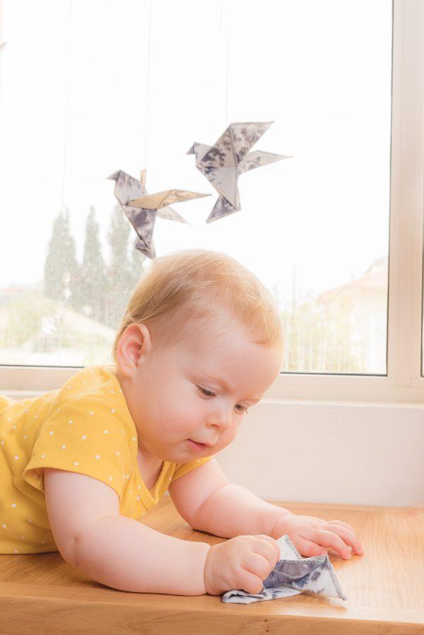 מובייל לתינוק ובו זוג ציפורי אוריגמי בד, מובייל אוריגמי, מובייל התפתחותי, זוג ציפורים על מקל, בד כותנה בצביעת טאי דאי, מתנת לידה, מובייל לעריסה. מורן אלחלל אוריגמי בד